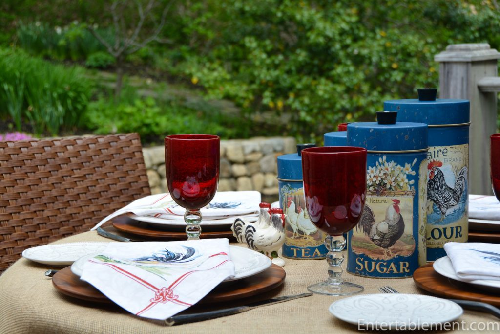 table set with rooster napkins, rooster canisters and blue glasses