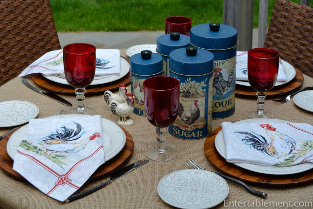 table set with rooster canisters, napkins and red glasses